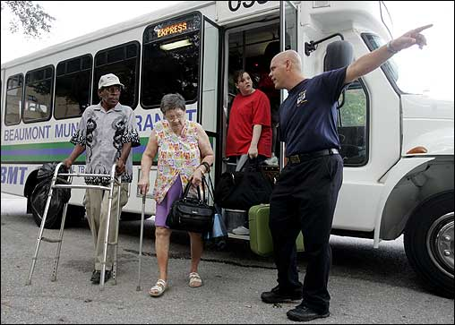 Beaumont firefighter James McLean (right) directed Ruby Manuel (center), 73, Allen Rideaux, 64, and other evacuees to a bus at the convention center in Beaumont, Texas, on Friday. The center was a departure point for residents who wanted to leave town before Hurricane Rita struck.