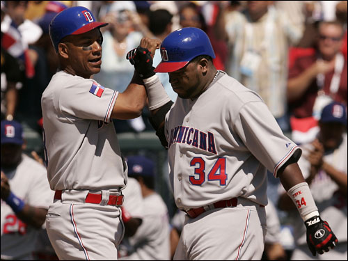 Dominican Republic teammates Moises Alou, (left) high-fived David Ortiz (34) after Ortiz hit a home run in the second inning during Round 1 play against Venezuela.