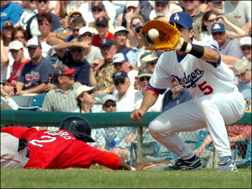 Red Sox baserunner Willie Harris dives back to first base safely avoiding being tagged out by Los Angeles Dodgers' Nomar Garciaparra in the second inning.