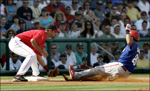 Red Sox third baseman Mike Lowell easily makes the tag out as Phillies Danny Sandoval slides in on a triple-attempt in the third inning.