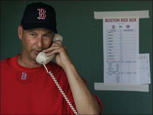 Red Sox manager Terry Francona talks on the phone prior to Friday's game against the Phillies in Fort Myers.