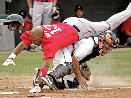 Enrique Wilson falls over Orioles catcher Brandon Marsters while being tagged out at the plate in the third inning.