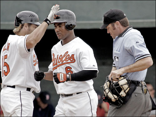 Baltimore Orioles Melvin Mora (No. 6) is congratulated by Kevin Millar at the plate during his third inning two-run homer against the Red Sox.