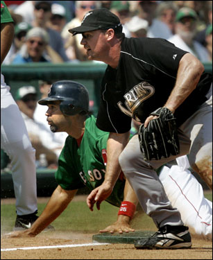 Red Sox base runner Mike Lowell hung onto the base as Marlins third baseman Mike Kinkade started to chase a ball he missed catching on a force attempt on a two-run double by teammate Alex Gonzalez. The Sox and Marlins played to a 5-5 tie.