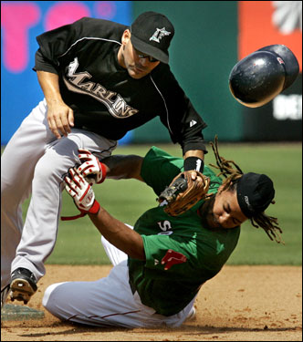 Red Sox base runner Manny Ramirez (bottom) lost his helmet as he slammed into Florida Marlins shortstop Robert Andino while sliding into second base on a single by Mike Lowell. Ramirez was safe on the play.