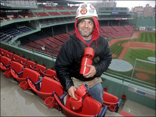 Scott Taylor, an American Seating employee, walked in Fenway Park holding new cup holders to install during preparation for Opening Day.