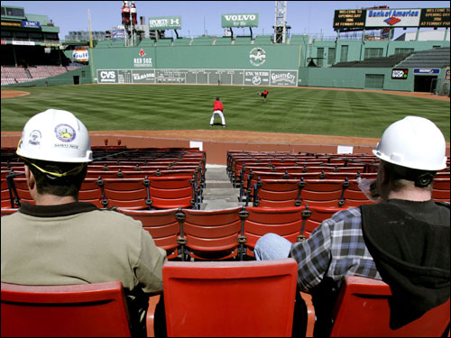 Laborers Scott Getchell (left) and John Gaspar, who have worked rebuilding Fenway Park in the offseason, ate their lunch as they sat in nearly empty stands and watched pitchers Josh Beckett and Keith Foulke work out on Monday.