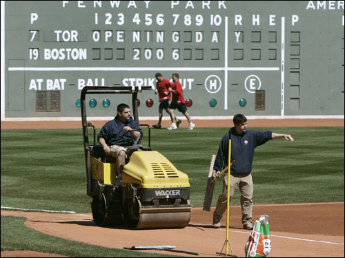 Grounds crew members prepared the field at Fenway on Monday. At rear running the warning track was injured outfielder Gabe Kapler and a member of the training staff.