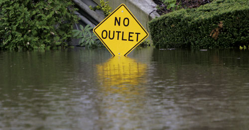 A partially submerged road sign is surrounded by water on a road near the confluence of the Merrimack and Nashua Rivers in Nashua, N.H.