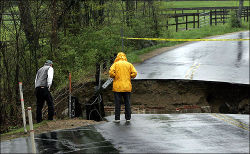 George Dixon, left, of Ogunquit, Maine, and Alex Scourtis, of Cape Neddick, peer at a collapsed road on the Ogunquit and Wells town line in Maine.