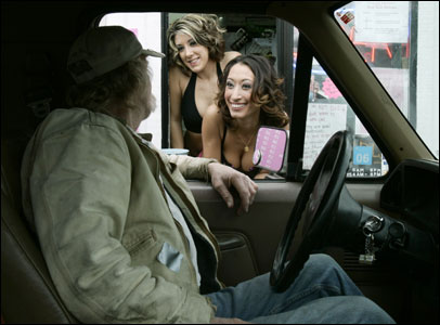 From left, baristas Toni Morgan and Candice Law talked to a customer at 'Cowgirls Espresso,' part of a chain of Seattle coffee shops that employ scantily clad women.