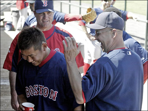 Red Sox manager Terry Francona (right) congratulated his starting pitcher Daisuke Matsuzaka while pitching coach John Farrell looked on at the end of the third inning against the Florida Marlins.