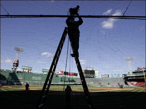 One of the many workers in action at Fenway on Monday.