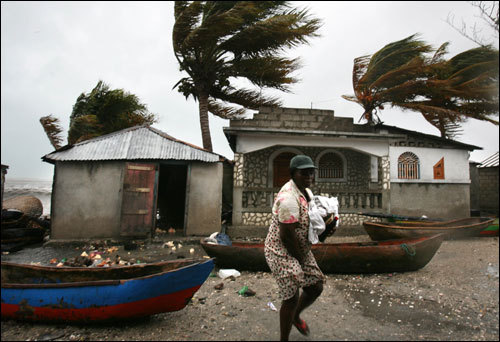 A woman leaves her house carrying some of her belongings during light rain and strong wind caused by Hurricane Dean as it moved along Haiti's southern coast on Sunday.