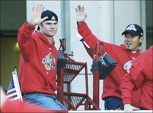 Pitchers Jon Lester (left) and Daisuke Matsuzaka wave to fans.