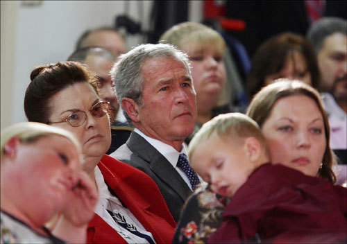 President Bush attended a Veterans Day ceremony at American Legion Post 121 in Waco, Texas, on Sunday. Malia Fry (right), wife of fallen Marine Gunnery Sergeant John Fry, held her 4-year old son, C.L., while Janie Shanks (left), John Fry's grandmother, looked on.
