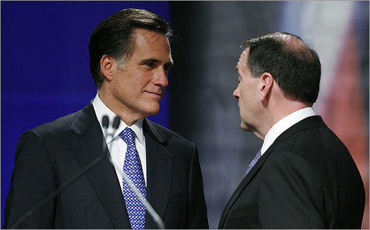 Republican candidates Mitt Romney and Mike Huckabee spoke together after the debate in Johnston, Iowa, yesterday.
