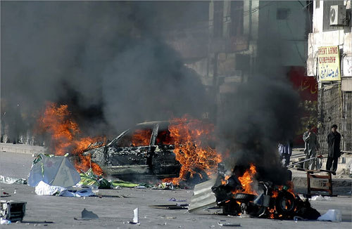 Smoke billowed from a burning vehicle and motorbike set on fire by angry supporters and demonstrators during a protest rally in Peshawar, Pakistan on Friday.