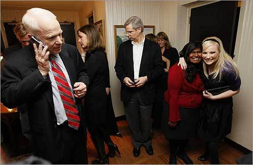 John McCain talked on his cellphone in his Nashua hotel room while his daughters, Bridget (left) and Meghan McCain, hugged and celebrated next to him.