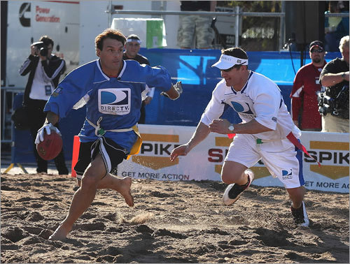 During the second half of the DirecTV Celebrity Beach Bowl on Thursday, Blue Team quarterback Doug Flutie evaded White Team player Merril Hoge. Flutie's team won, and he was named the game's most valuable player.