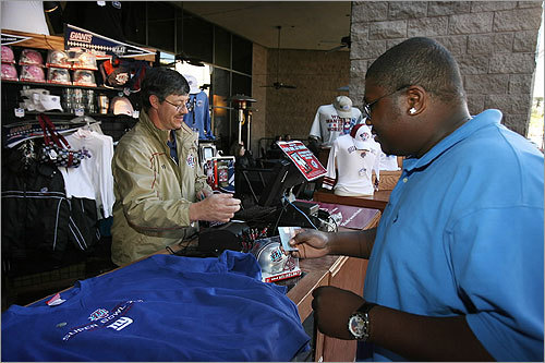 Across from the Phoenix Convention Center Thursday, Tim Washington (right), of Phoenix, bought a Giants logo sweatshirt as Geoff Porter, of Shrewsbury, rang him up at an NFL merchandise stand.