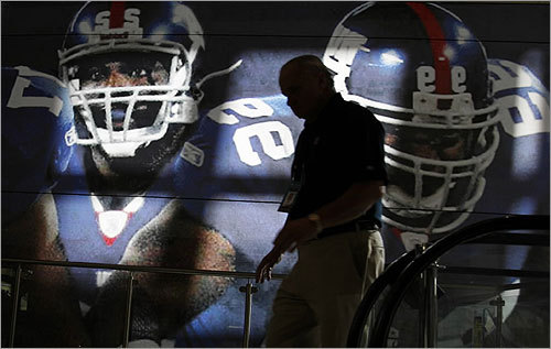 A man walked by a translucent banner depicting the New York Giants at the Phoenix Convention Center Wednesday.