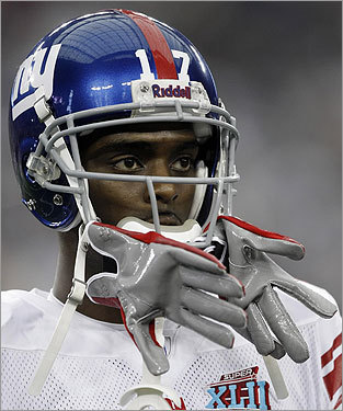 Plaxico Burress, with his gloves stuck in his helmet, looked on before the start of the game.