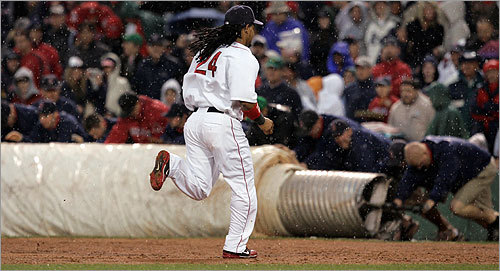 Manny Ramirez headed for the dugout as the grounds crew rolled the tarp over the infield for a rain delay during the eighth inning.
