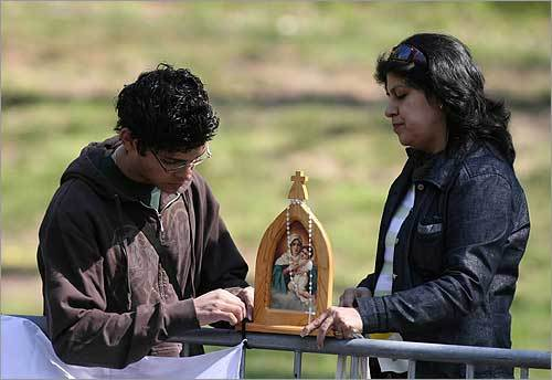 Josue Iseas (left) and Sofia Delgado (right) tied down a wooden statue of Mother Thrice Admirable Queen and Victress of Schoenstatt before the arrival of Pope Benedict's motorcade along Massachusetts Avenue.