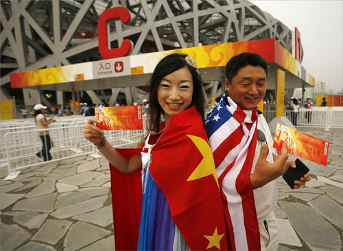 Carrie Dong from Beijing (left) and Chinese Jay Jingdong Ouyang, who lives in New York City, posed with Chinese and American flags as they held their tickets and prepared themselves for the opening ceremonies.