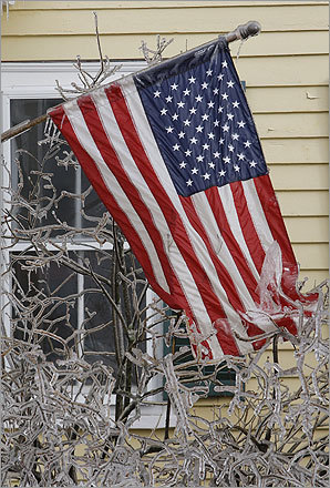 A frozen, ice-covered American flag hangs on a house in Princeton, Mass.