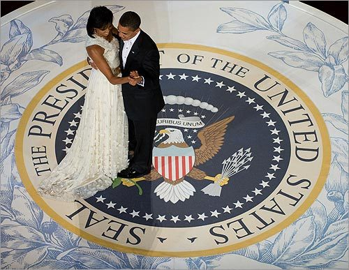 First Lady Michelle Obama and President Barack Obama glided across a replica of the presidential seal during a dance at the Commander-in-Chief's Inaugural Ball. The first lady's white chiffon, one-shoulder gown, covered in fluffy appliques and beading, was designed by 26-year-old Jason Wu. It was considered surprising for its reserve given Michelle Obama's love of jewel tones and sleek silhouettes.