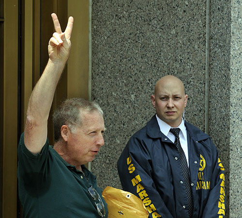 Victim Michael DeVita gives the victory sign as he leaves United States Courthouse in New York June 29, 2009 after Bernard Madoff received 150 years in prison for his multibillion-dollar fraud scheme.