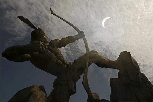 In China, a statue of the legendary Chinese hero Houyi, who shot down nine suns with his bow and arrow, is silhouetted against a partial eclipse in Changzhi, Shanxi, China.