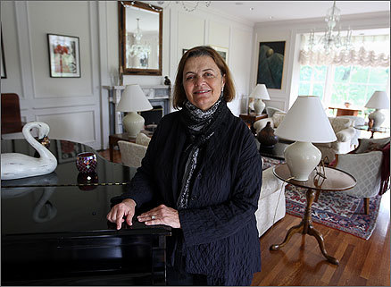 Wellesley College President Kim Bottomly stood inside the living room of her home, 735 Washington St., Wellesley, which is adorned with some of her art.