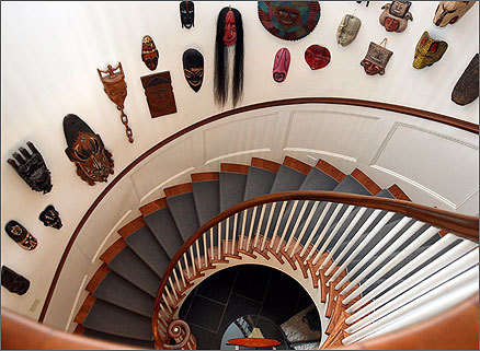 A collection of masks wrap around a spiral staircase in Bottomly's home. Built in 1854, the Webber-Durant Estate has been used as a president's house since 1926.