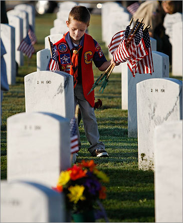 Boy Scout John Myers, 7, placed flags today at cemetery headstones for Veterans Day at the Central Texas State Veterans Cemetery outside of Fort Hood in Killeen, Texas. Just a week earlier, a gunman killed 13 at Fort Hood.