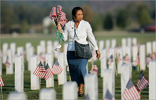 Tina Atkins, wife of a Fort Hood soldier, placed flags at cemetery headstones for Veterans Day at the Central Texas State Veterans Cemetery outside of Fort Hood.