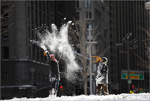 Children played with snow in the middle of the traffic roundabout at Columbus Circle in New York.