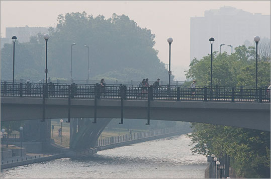Commuters make their way over the Rideau Canal as a think layer of smoke covers the Ottawa area on Monday May 31, 2010. The smoke is coming from more than 50 forest fires burning in central Quebec.