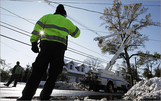 A police officer directed traffic as a work crew repaired power lines in South Hadley. Millions of people from Maine to Maryland remained without power on Sunday.