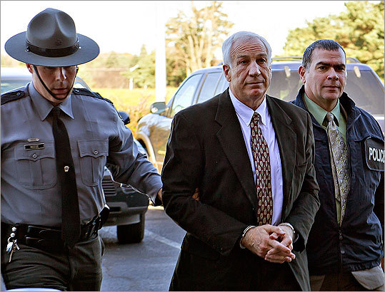 Former Penn State football defensive coordinator Gerald 'Jerry' Sandusky, center, arrived in handcuffs at the office of Centre County Magisterial District Judge Leslie A. Dutchcot while being escorted by Pennsylvania State Police and Attorney General's Office officials on Saturday, Nov. 5, 2011, in State College, Pa.