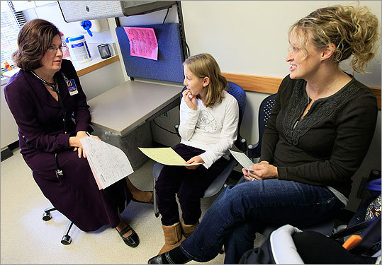 Dr. Elaine Urbina, left, goes over test results with Joscelyn Benninghoff, center, 10, and her mother Elizabeth Duruz, at Children's Hospital in Cincinnati. Benninghoff is taking medication to control her cholesterol.