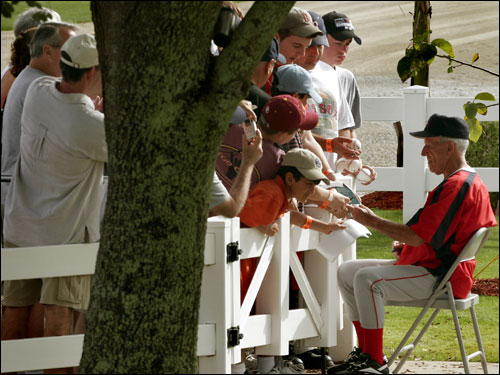 Red Sox great Johnny Pesky signed autographs for fans under the shade of a tree.