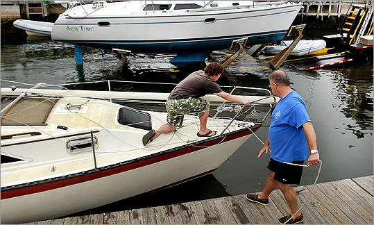 Boat owners rushed to get their boats out of the water early Saturday morning at the town boat ramp in Mattapoisett. During Hurricane Bob in 1991, many boats were damaged when they washed up onto the landing because of the high winds and tidal surge that put 7 feet of water into the parking lot.