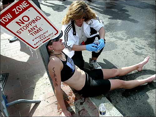 After fighting the heat and finishing the race, Sara Vergote can't help but stop and rest on the side of the road.