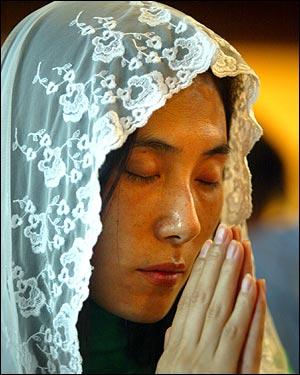 Nammi Lee of Belmont prays during Mass at St. Philip Neri Church.