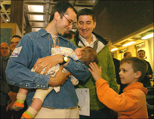 Christian Schlesinger (left) and Russ Irwin smile at their daughter, 8-month-old Nina Porter, while they wait in line at City Hall to apply for a marriage license. Buster Coen, 8, a friend of the family, is at right.