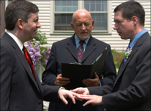 Stuart Wilder Wells lV (left) and Lawton Phillips Bourn exchange rings and vows on their front yard in Rowley.