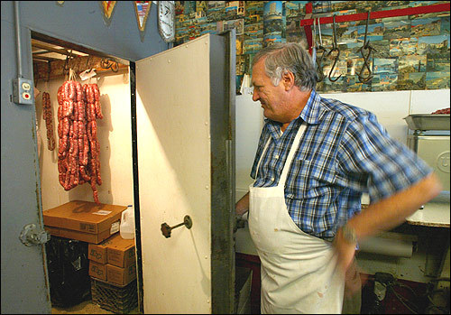 Susi's father, Frank, owner of Abruzzese Meat Market on Salem Street, checks his supply of fresh sausage. For most of Boston and beyond, the North End means restaurants, and Frank Susi has been supplying them with meats for 42 years. His customers include several generations of families.